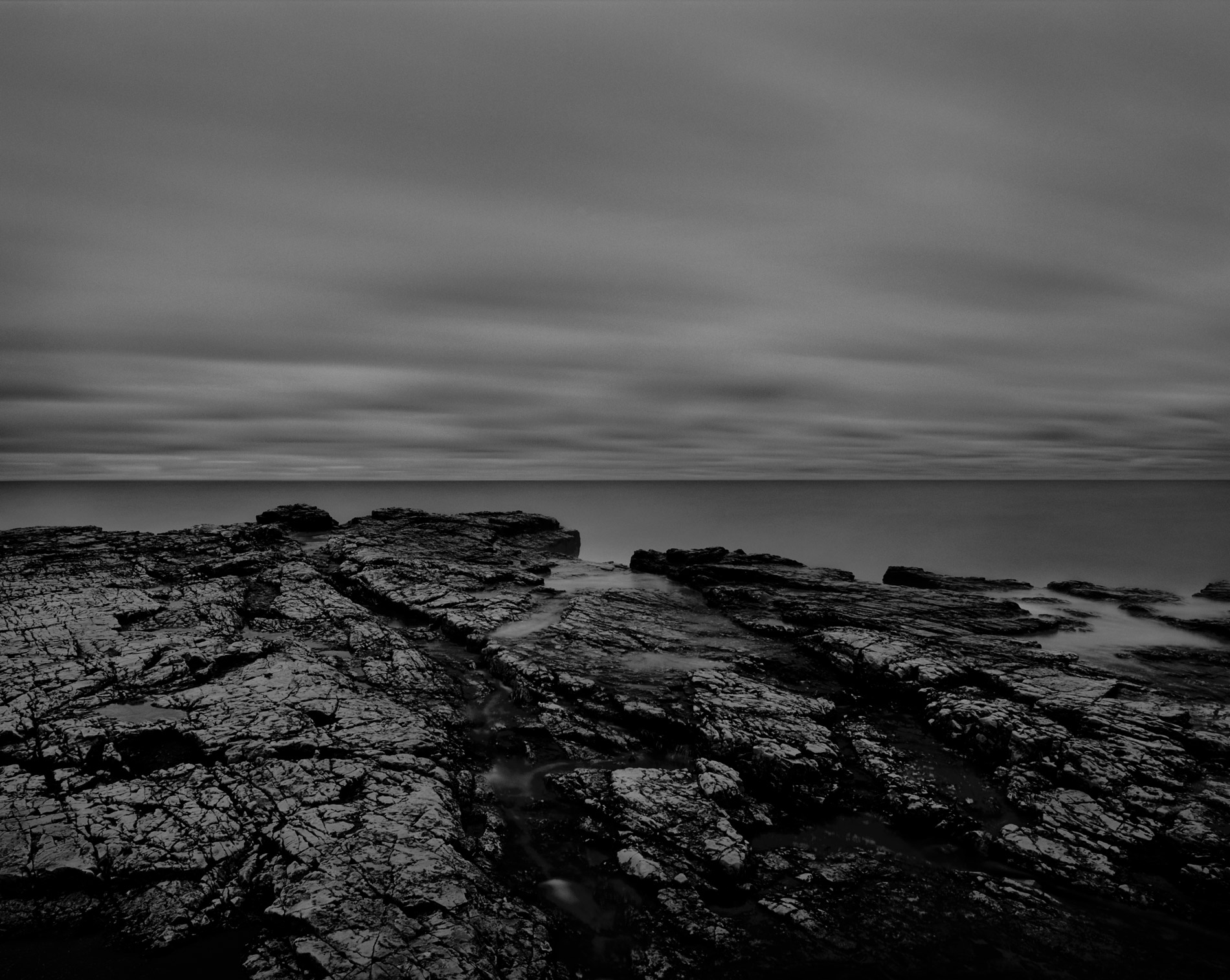 Black rocks in water dark sky fine art photography copyright Kenneth Rimm