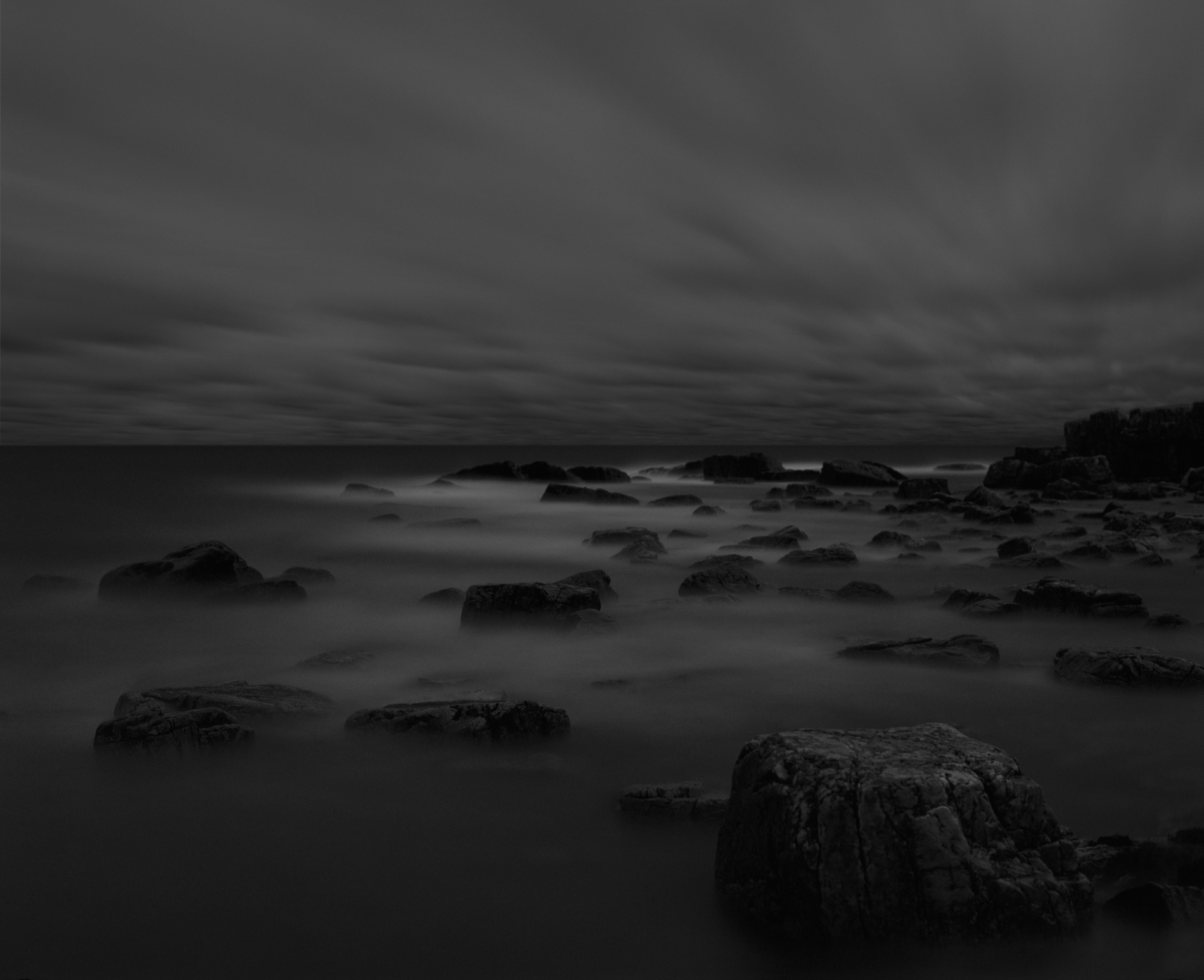 Black rocks in water dark sky water motion copyright Kenneth Rimm